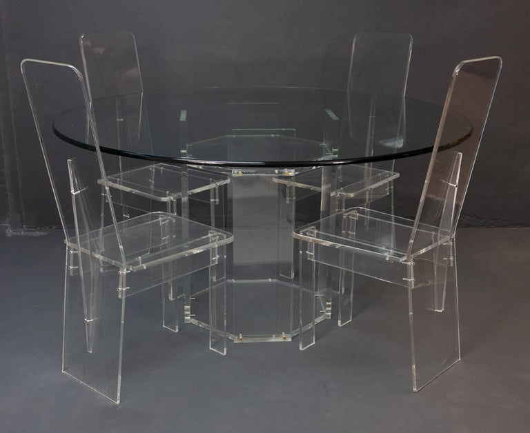 Lucite dining room set consisting of four high back dining chairs with a matching dining table. The large dining table features a thick glass top, with a beautifully rounded edge which matches the edges on the chairs. This set is made of a clear