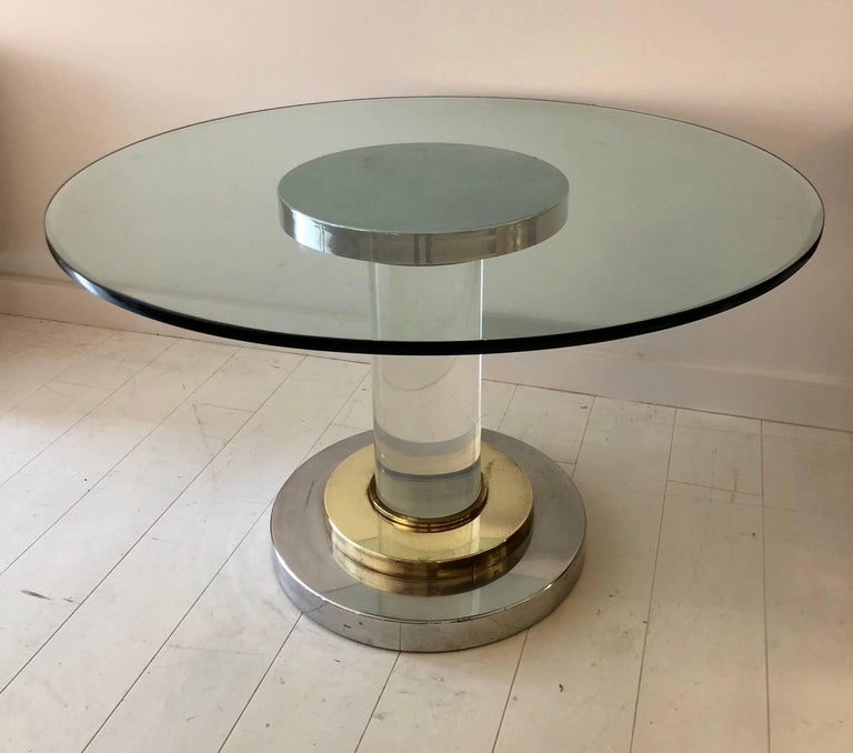 "Center or dining table composed of a chic mix of polished brass, chromed steel and 8"" D solid Lucite, with a 1"" thick plate glass top, circa 1970."