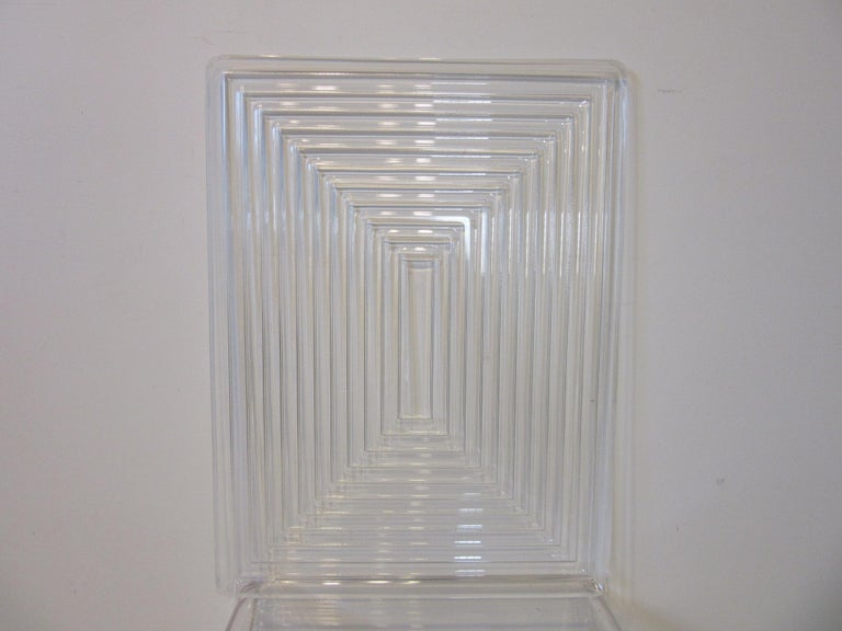 A large well crafted Lucite serving tray with raised horizontal and vertical line designs getting tighter towards the center giving the piece a sophisticated look in the manner of Eliel Saarinen and Art Deco.