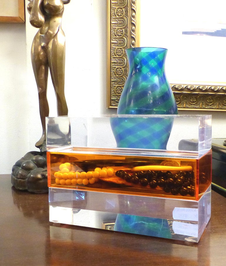Offered for sale is a clear and orange Lucite trinket or jewelry box. The box offers a sleek storage solution with an orange compartment sandwiched between two thick slabs of Lucite. The top section is the lid which lifts off.