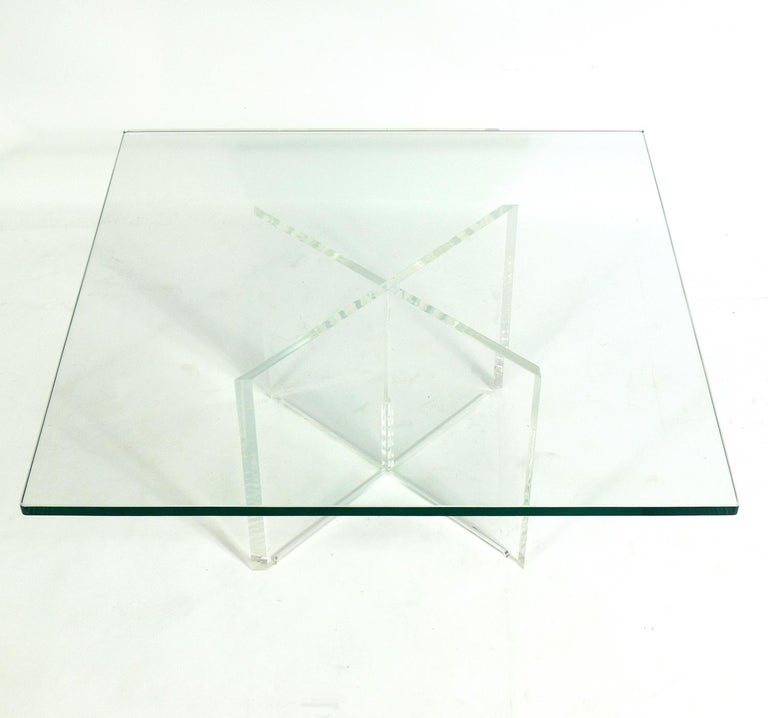 Lucite X-base coffee table, American, circa 1970s. It is well constructed with a chunky Lucite or acrylic X-form base and a thick glass top.