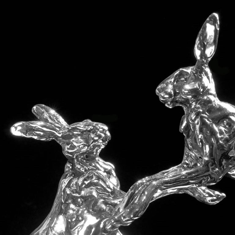 A 'Leaping Hares' sterling silver sculpture by Lucy Kinsella, the limited edition finely modelled pair of long eared hares caught mid confrontation with one stood tall on stretched hind legs, the other leaping through the air, front legs