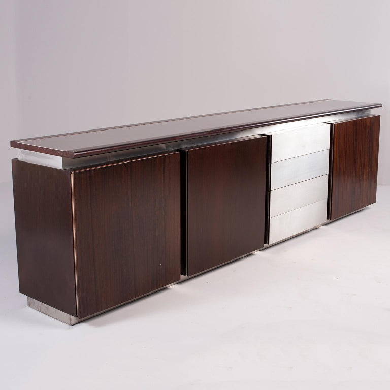 Sideboard or credenza designed by Ludovico Acerbis for Acerbis of Italy, circa 1970s. Dark rosewood with contrasting stainless steel trim and drawers. Three storage compartments with hinged doors and adjustable internal glass shelf and one set of