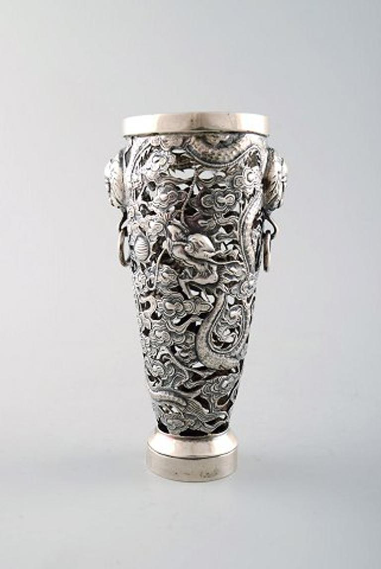 Luen Wo, Shanghai. A pair of dragon vases in silver, circa 1900. Pierced body with handles in the form of masks. In very good condition. Stamped. Measures: 11.5 x 6 cm.