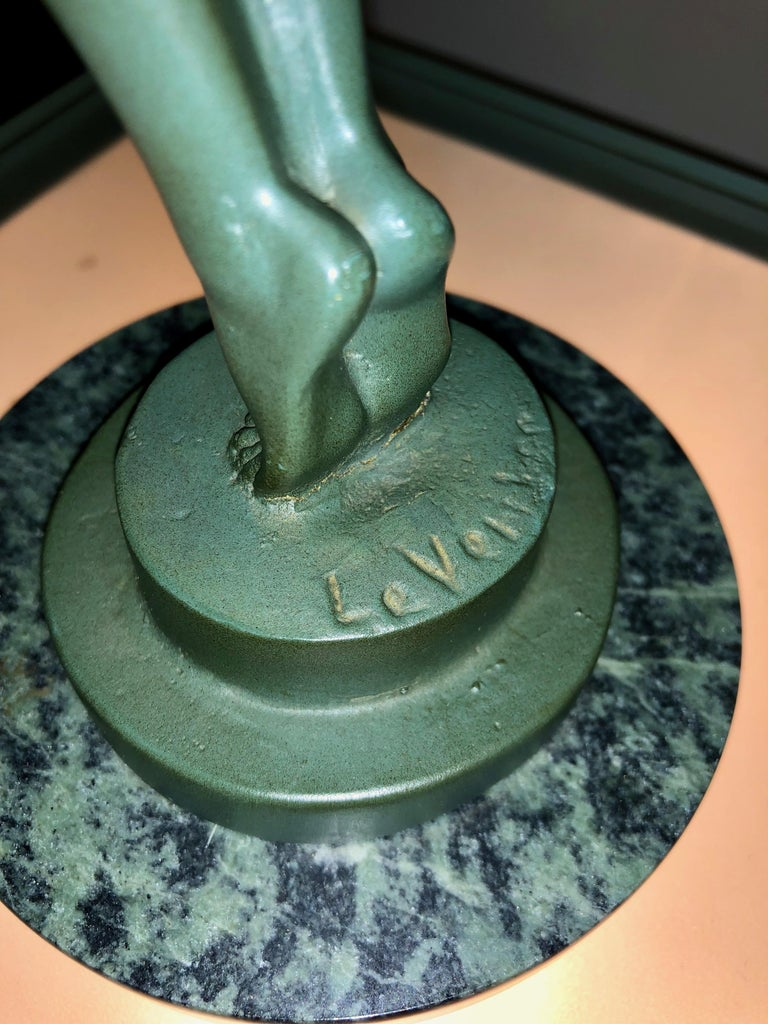 Iconic of all Art Deco sculptures. Created by Max LeVerrier in 1928, the dark green patinated petite bronze figure of a slender woman holding a globe aloft and standing on a marble pedestal is possibly the most famous image of the period.