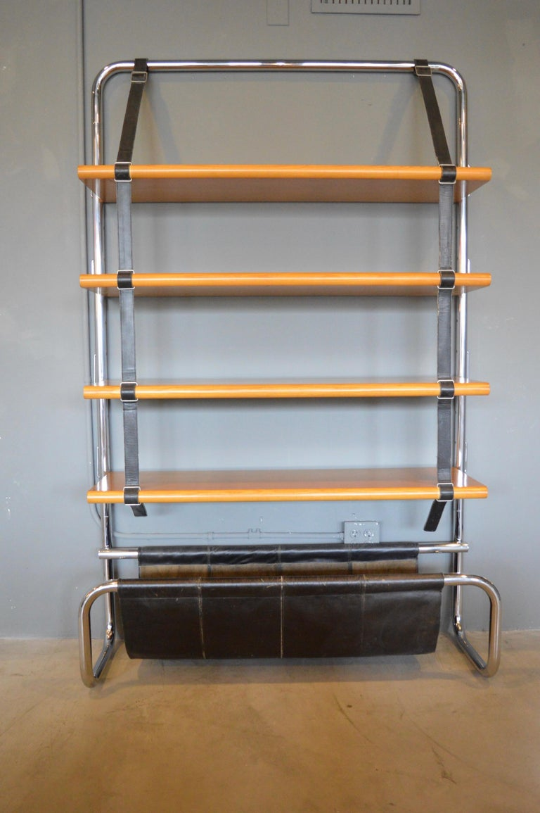 Stunning chrome, leather and wood bookshelf by Luigi Massoni for Poltrona Frau. Made in 1971, featuring tubular chrome frame, with five oak shelves, black leather straps and leather catchall at the bottom. Shelves are suspended by saddle leather