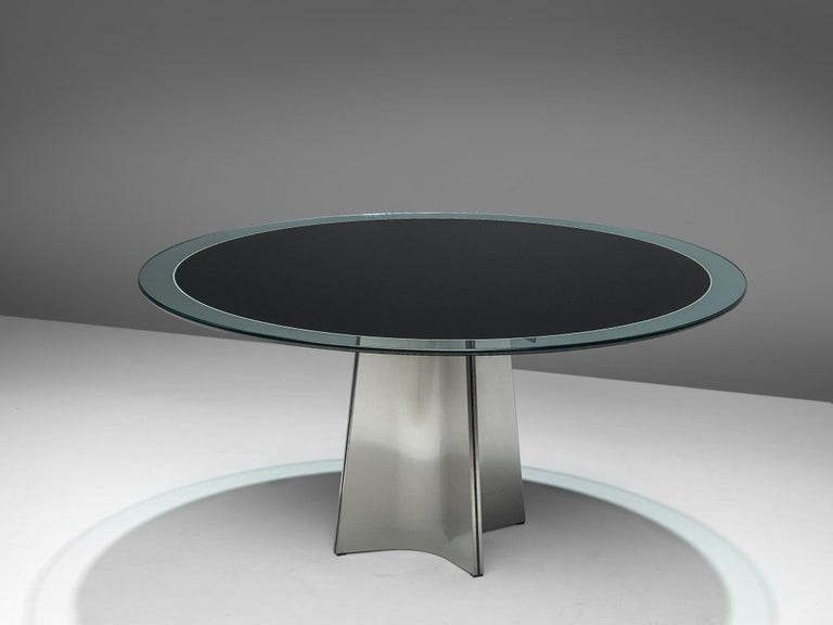 Luigi Saccardo for Armet, round dining table, glass and metal, Italy, 1970s.  Round pedestal dining table in brushed aluminum. A circular clear glass top, with a dark center. The base is formed of four concave curved plates of metal, which combine