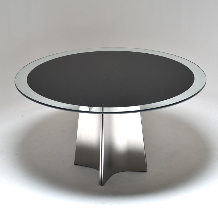 Round pedestal dining table, designed by Luigi Saccardo, for Armet, Italy, 1970. The base is made of four brushed stainless steel plates, pressed to form a cross. The top is a thick round clear glass, black lacquered (underside). Very graphical