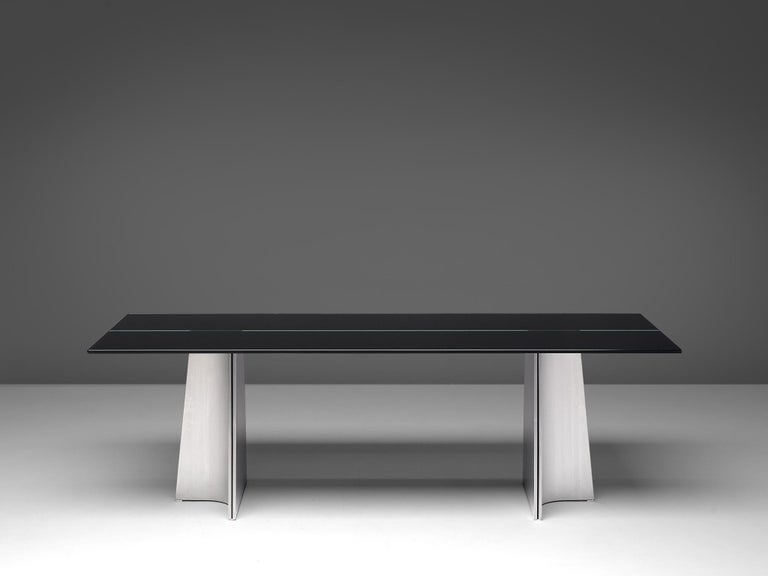 Luigi Saccardo, dining table model 'Ufo', metal and glass, Italy, 1970s  Sculptural Postmodern dining table or desk, named Ufo, by Luigi Saccardo. The base consists of two legs which are formed of two concave curved plates of metal and one
