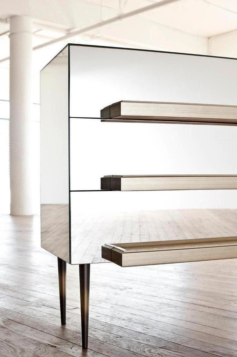 The traditional French mirror cabinet is reinterpreted leaving the mirrors frameless and exaggerating the molding to be used as the handle.