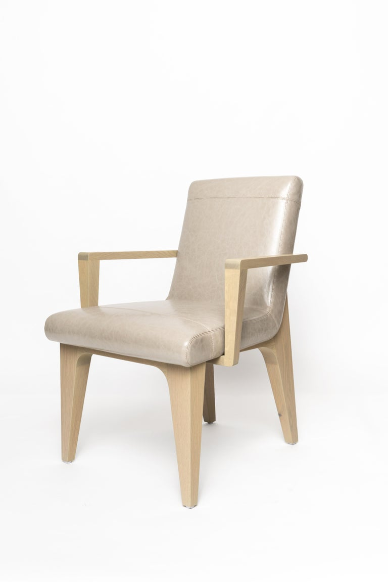 The LUMA design workshop Silo armchair is the result of thoughtful design and expert craftsmanship. LUMA tan faux leather, stone oak, and nickel, come together elegantly to create a comfortable, modern dining chair. The metal detailing and unique