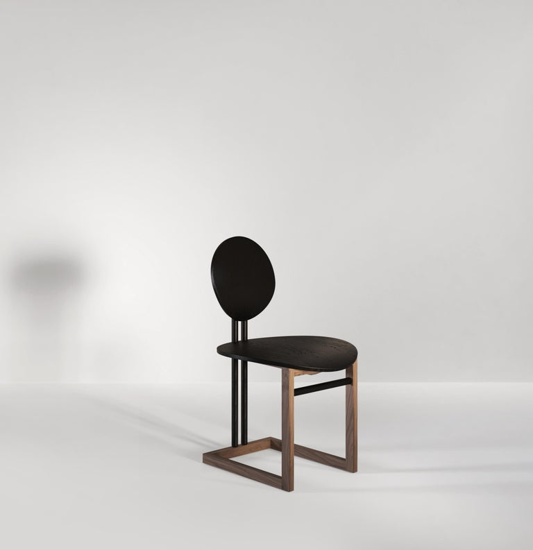 A handcrafted wooden dining chair inspired by vintage forms and contemporary techniques. Two almost-circles acting as the backrest and seat offering comfort and style. The structure holding the chair is in a contrasting wood and is designed with