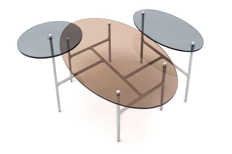 Reminiscent of the Apollo Lunar Rover, the delicate frame of the Luna nesting table lifts three eclipsing discs of tinted glass, playing with layers of transparency. The perpendicular array of integrated legs and braces balance the triad of
