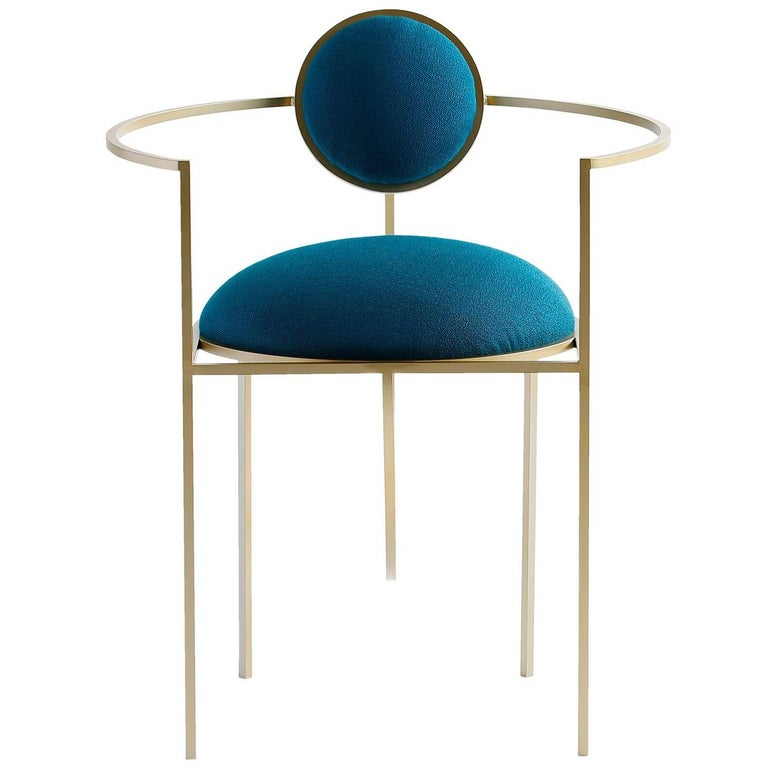 The Lunar chair is distinguished by two enveloping crescents for armrests, and a smaller backrest which, like a moon, circles its planet on an orbit of its own. Constructed from thin square rod, the chair is elegant, modern, minimal and delicate. It