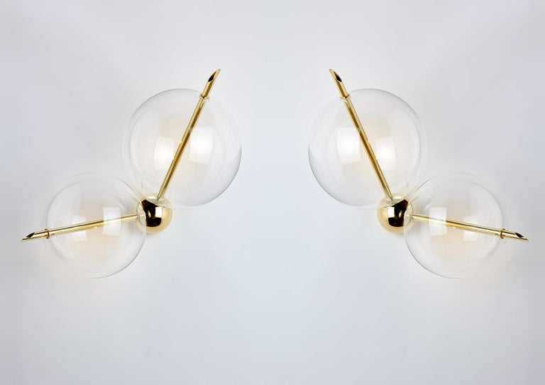 Lune two lights is composed of one solid brass sphere and two handblown glass globes. The light gets out from the two brass rod crossing over the spheres, and through them, it is diffused softly creating a pleasantly reflecting on the side. Lune