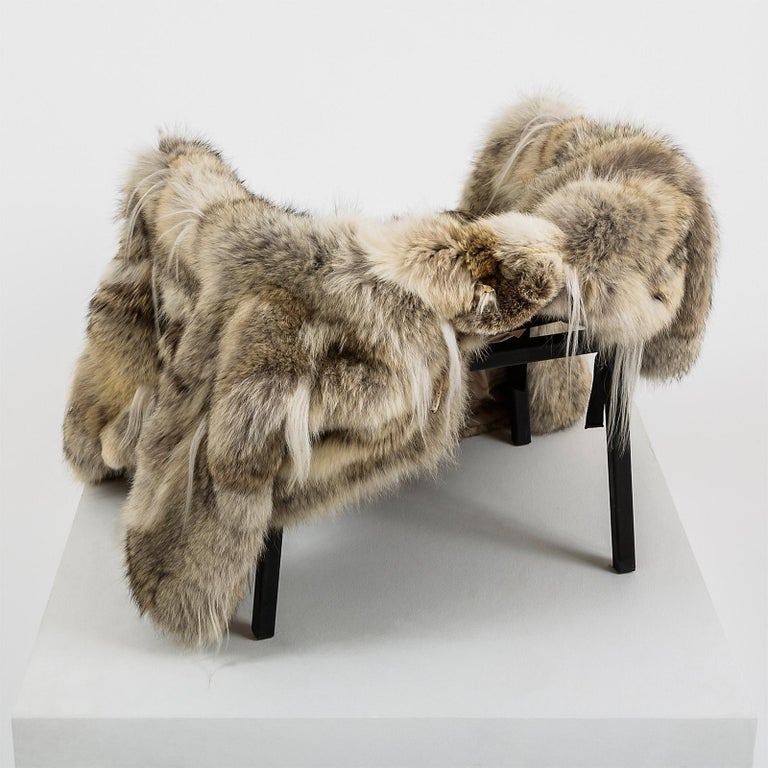 A black steel chair frame. A fur coat (wolf, goat) in size M/ L. The coat has straps attached to convert it into a seat, thus making the chair functional and complete.  Materials: Steel chair frame and fur coat Edition: Unique piece Year of