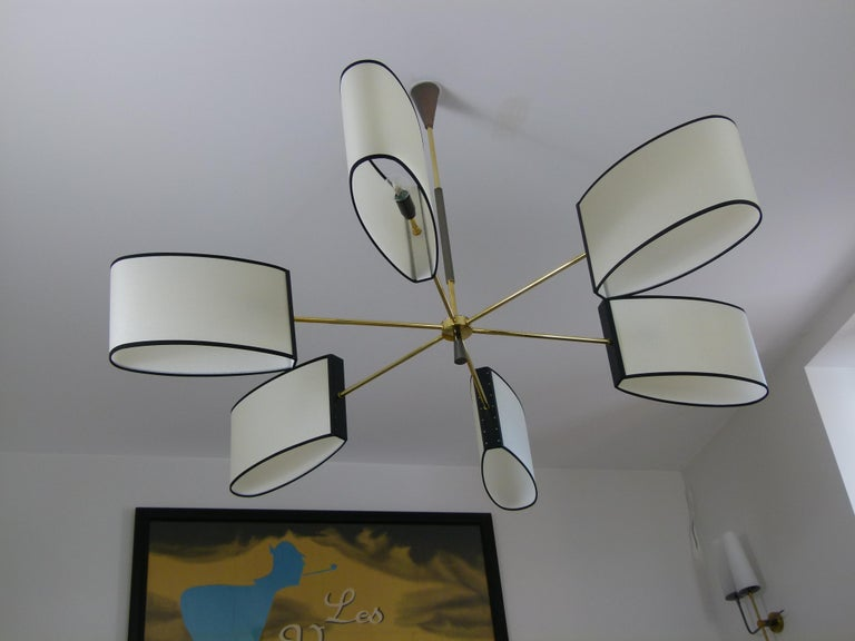 Circular brass chandelier, consisting of a circular brass base, on which are arranged six brass sconces. Each arm has a black lacquered metal plate supporting an oval lampshade. A brass rod interposed by a brass fluted gun barrel patina connects the