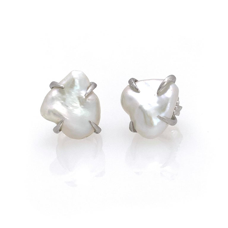 Beautiful pair of lustrous white baroque pearl stud earrings. The pair measures 12-13mm width, handset in platinum rhodium plated sterling silver (matte finish). Straight post with large friction back allowing the earrings to sit well on the ear.