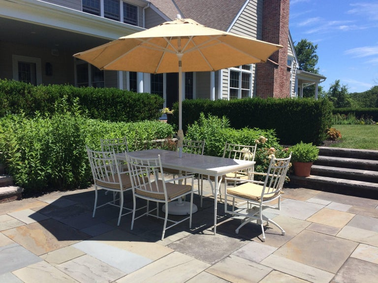 Stunning large rectangular outdoor dining table and six matching chairs in white cast aluminum, having very large umbrella and custom seat cushions upholstered in Sunbrella. The two chairs at the head swivel.  Summer Classics. Measures: Chairs are