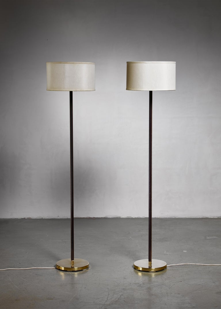 Luxurious, minimal floor lamp by J.T. Kalmar, Austria, with heavy brass and leather covered stem.  We have a large number of these floor lamps available, the simple, yet rich and elegant base can be customized with variations in the shade.   The