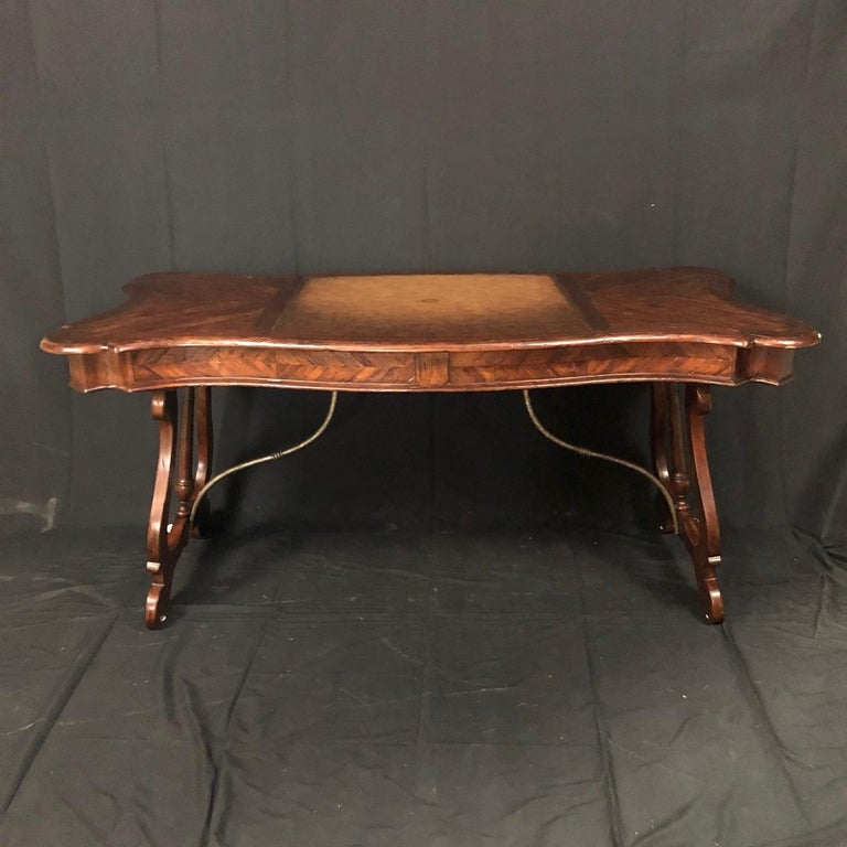 An antiqued mahogany writing table, desk or bureau plat having serpentine parquetry planked top inset with a central burnished and hand tooled leather writing surface above two frieze drawers, on splayed lyre supports with a baluster turned central