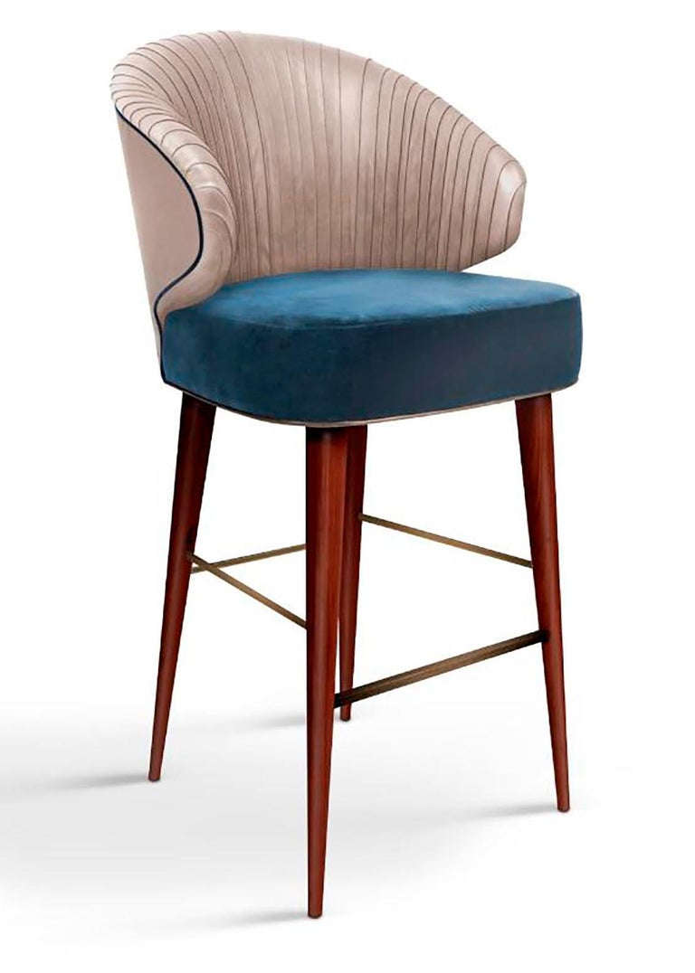 The Colorado bar chair comes with a pinewood structure holding a high-class upholstered cotton velvet, standing on walnut wood legs that are covered with aged brushed brass accents. Being a beautiful and curvaceous chair, with an extremely elegant