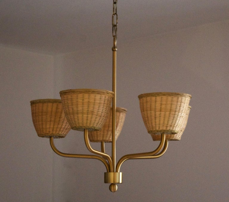 A chandelier light. By Luxus, Sweden, 1970s. In brass. Assorted vintage rattan lampshades.  Five-armed and features transparent plastic sockets. Stated height includes full drop.  Other designers of the period include Axel Einar Hjorth, Roland