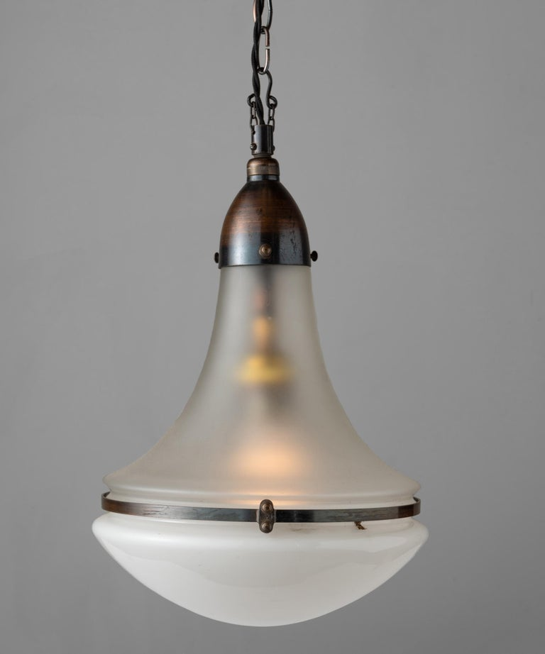 Luzette pendant by Peter Behrens, Germany circa 1930.  With frosted glass top and opaline glass bottom, secured with copper fitter and brace. Manufactured by AEG Siemens with manufacturer's mark.  Measures: 9