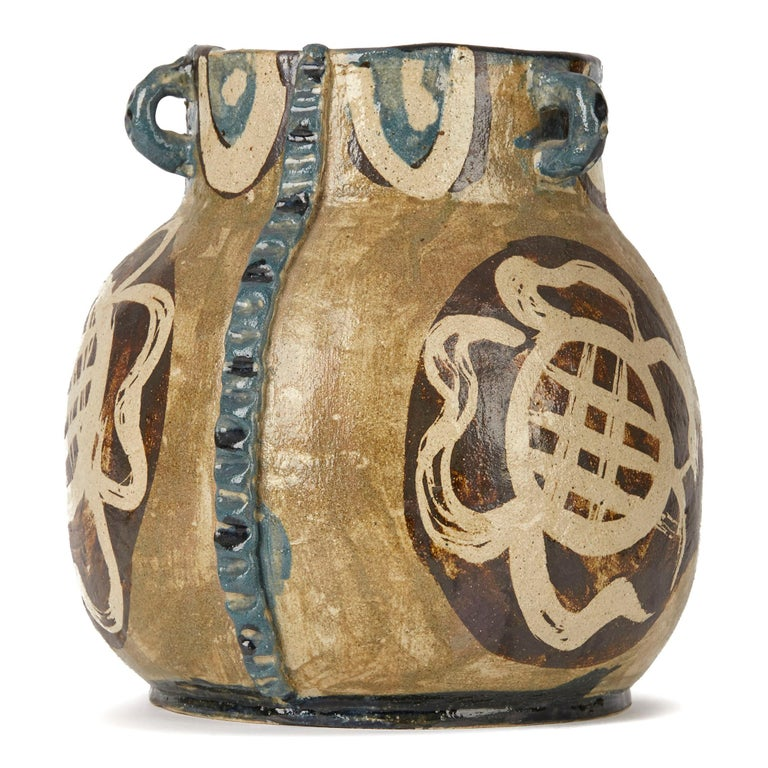A rare studio art pottery vase of rounded bulbous shape applied with three loop handles and with vertical crimped stems by Lydia Corbett (Sylvette David). The heavily potted vase is hand painted in tones of brown and blue on a natural glazed ground