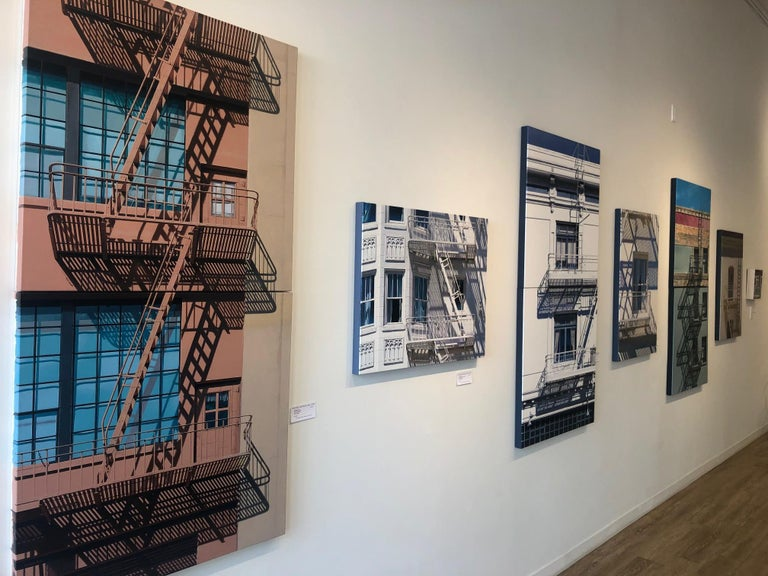 '20/20 Vision' depicts a historic San Francisco warehouse building with warm sunlight and shadows cascading across the facade of the building with blue inset window panes. The subtle and brilliant work of art is meticulously hand painted by Lynette