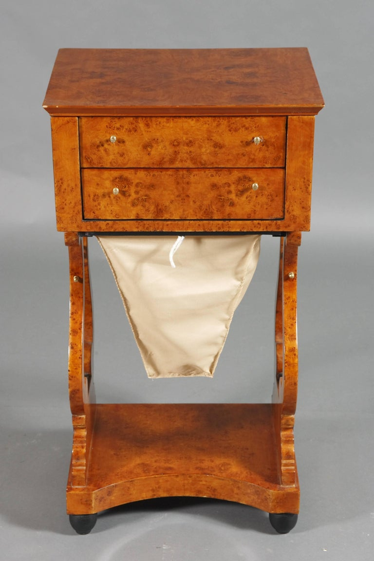 Bird's-eye on solid conid beechwood. Straight, bipedal base on lyre-shaped, perforated cheeks with metal sides. Underneath pull-out woolen drawer. Four-sided base plate. Top drawer with compartment. Overlapping, rectangular, fold-up plate.