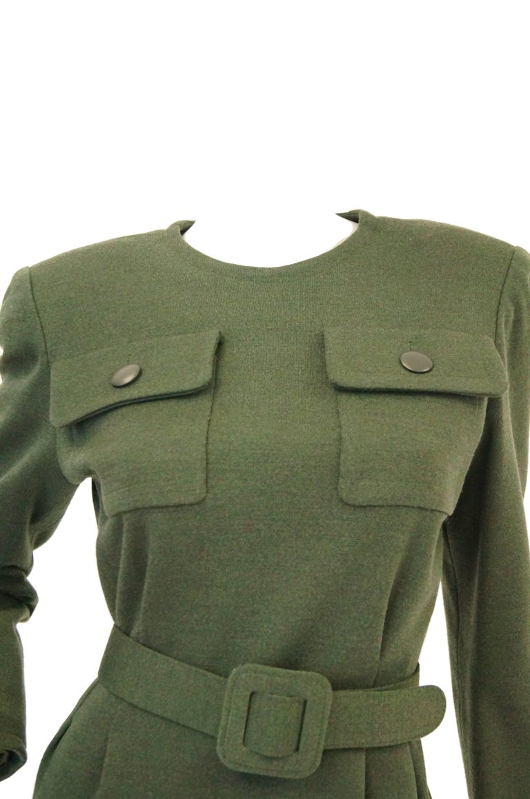 Understated and versatile olive green wool dress by Hubert de Givenchy. The dress hits at the knees, is long sleeved, and has a tight jewel neckline. The dress features two button closure flap pockets at the bust, a wide waist - cinching belt with