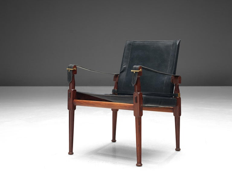 Wonderful 'Safari' lounge chair, wood, black leather and brass, Pakistan, 1970s.  This 'Safari' armchair shows very elegant and well designed lines, in combination with carefully crafted wood joints. The black leather with multiple straps completes