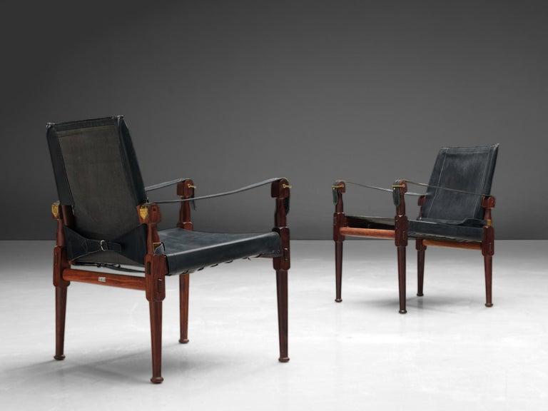 Wonderful 'Safari' lounge chairs, wood, black leather and brass, Pakistan, 1970s.  This 'Safari' armchair shows very elegant and well designed lines, in combination with carefully crafted wood joints. The black leather with multiple straps completes