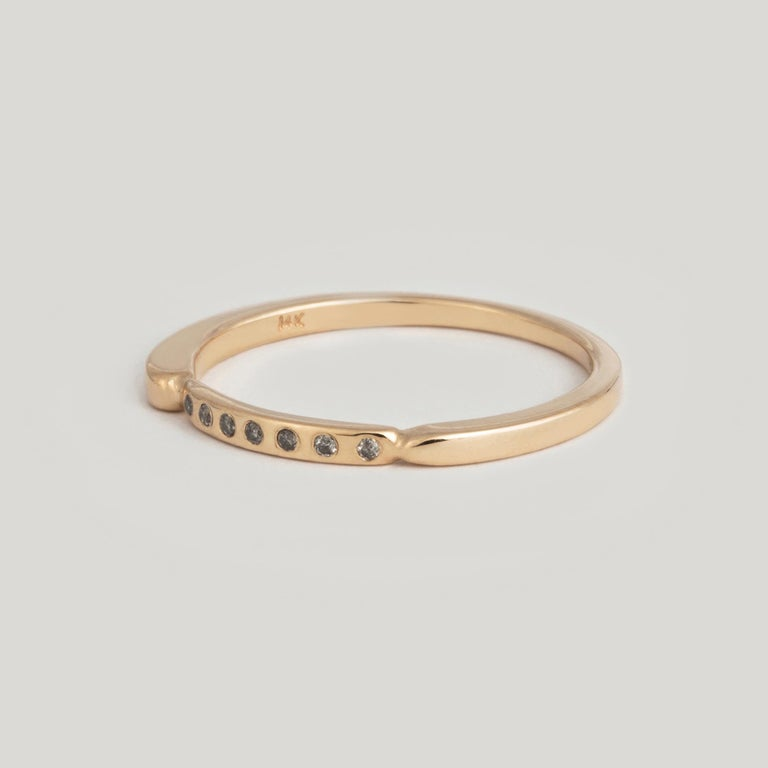 The magic of seven: Seven colors in a rainbow. Seven layers of the feminine existence. Seven deadly sins... in a beautiful band encrusted with seven grey diamonds. The flat profile of this band makes it perfect for stacking alongside others in your