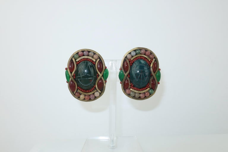 These exotically styled earrings from M & J Hansen are a black resin base accented by dark green carved stone scarabs surrounded by glass beads replicating rose quartz and carnelian.  A textured chain border adds to the design which is reminiscent