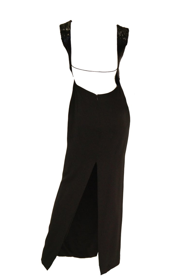 Elegant 1990s black silk evening dress by Richard Tyler. This maxi length dress has a shift silhouette that skims the body, a wide bateau boat neck, and capped sleeves with hand detailed black sequins. The amazing deep plunging back of the dress is