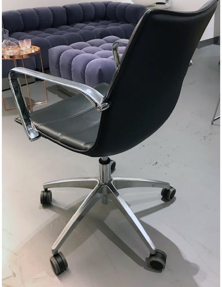 Padded and upholstered swivel chair with plywood beech inner shell, seat aluminium armrests, gas height adjustment, PC1 die- cast polished aluminium base. Dimensions: H 32.6