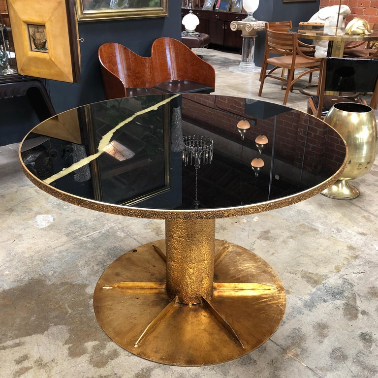 Italian round brass dining and central table. Hand beaten brass base in worked brass and black glass hand-painted top.