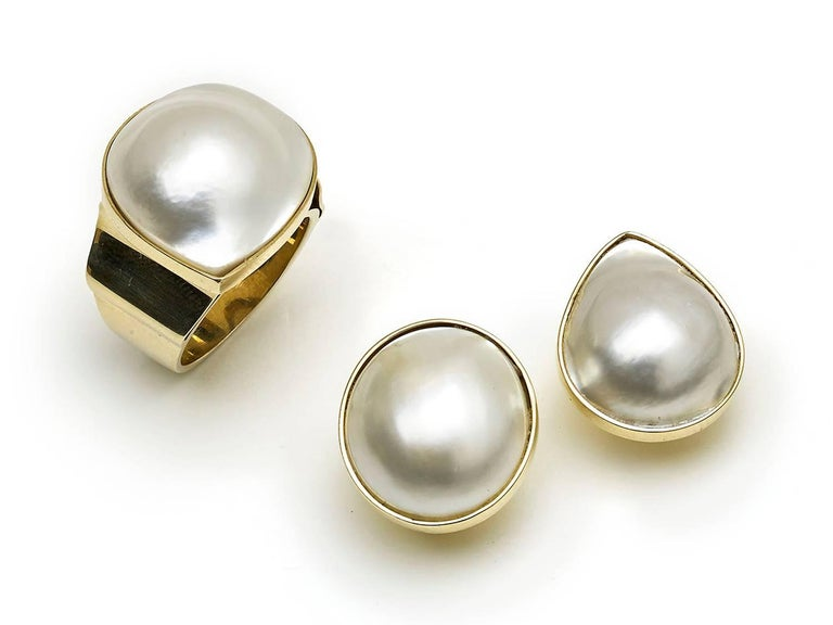 A mabé pearl and gold earrings and ring suite, with a ring, set with a pear shape mabé pearl, in a rub over setting, on a wide, tapering, shank, mounted in 14ct gold, stamped 14K and a pair of earrings, set with one oval and one round mabé pearl, in