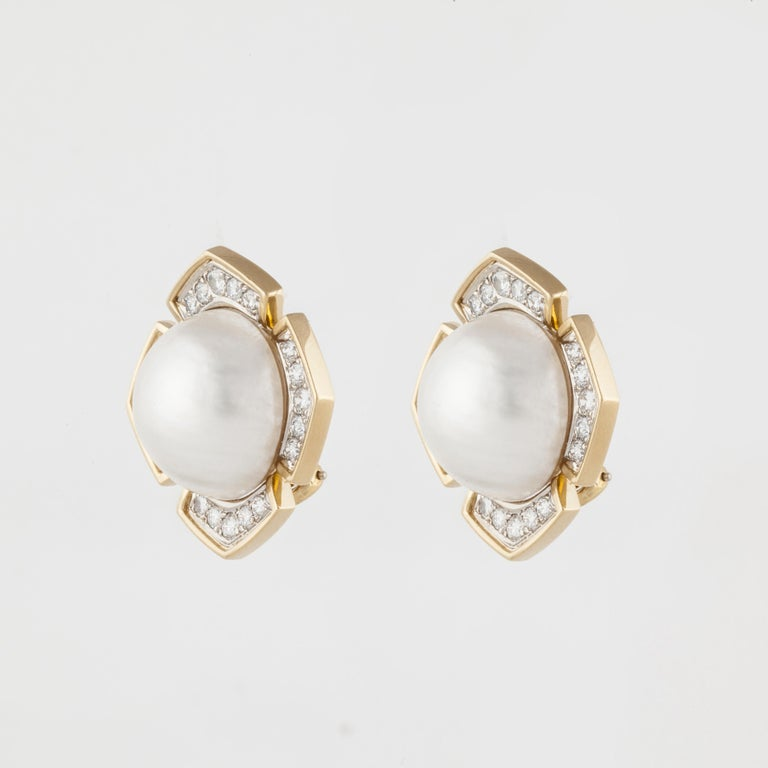 18K yellow gold earrings.  Each is set with a cultured Mabe' pearl measuring 17-17.5mm.  Surrounding the Mabe' pearls are a total of forty (40) round diamonds weighing 2.10 carats; they are G-H in color and VS1-VS2 in clarity.  Measure 1-1/8