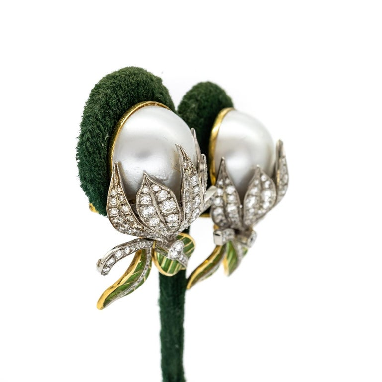 A pair of Moira bud earrings, with mabé pearls, measuring approximately 16mm, with pavé set round brilliant-cut diamonds and green plique à jour enamel leaves, mounted in gold, with white gold settings. Signed and numbered. Moira's eponymous