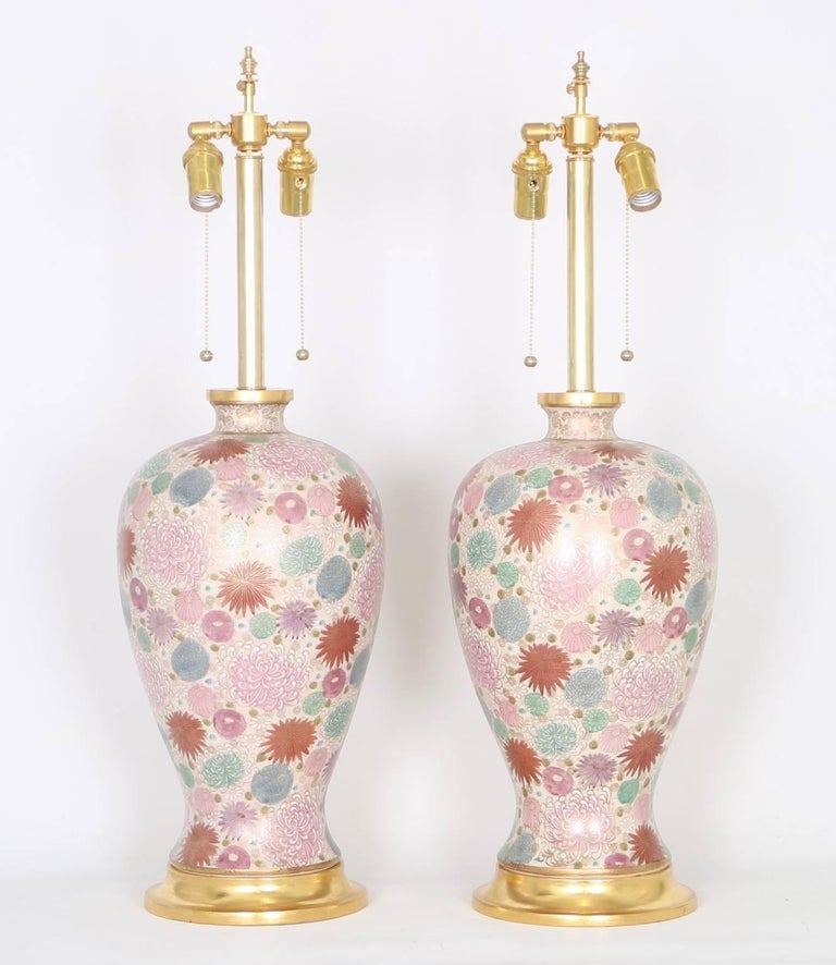 Hollywood Regency Japanese vase table lamps with a chrysanthemum motif in soft pink, mauve, mint, violet and powder blue hues mounted on gilded bases by Mabro. The lamps have been fully restored with all new wiring and hardware including a double
