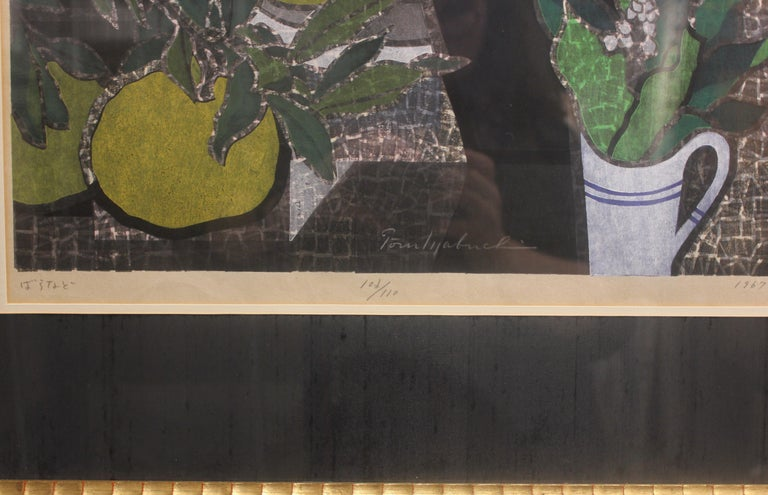 Woodcut print of a vase with flowers. The work is signed by the artist and dated. It is framed in a gold frame with a dark blue matte.  Artist Biography: Mabuchi Toru was born in 1920 in Tokyo as the son of a woodblock engraver and artist. His