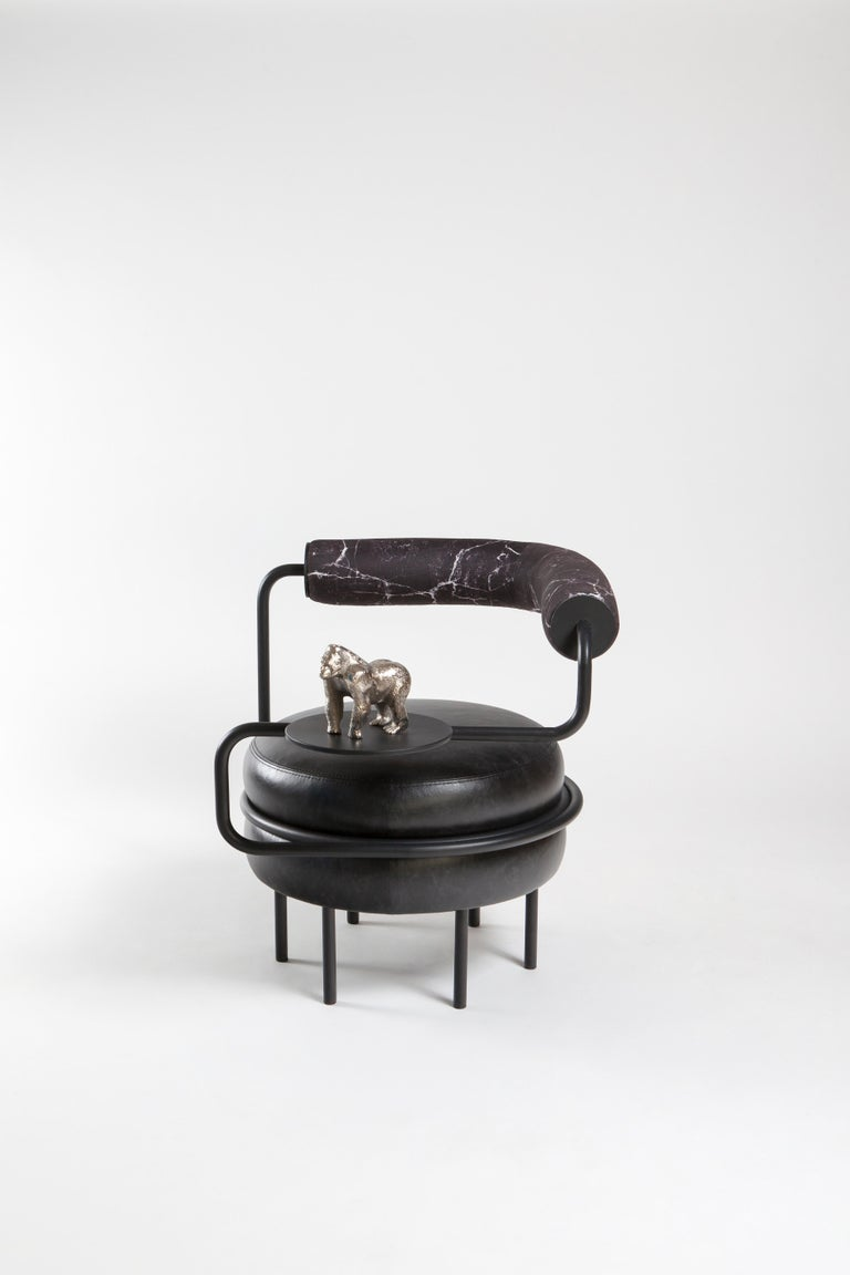Kontra's interpretation of Macaron.  One armed leather chair provides comfortable seating with a side table of It's own.