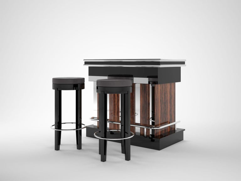 A design bar made of Macassar wood and piano lacquer and two stools with a suede upholstery. The lower part of the bar and the top of the top has been painted with a deep black piano lacquer and polished to a high gloss. In between is a beautiful