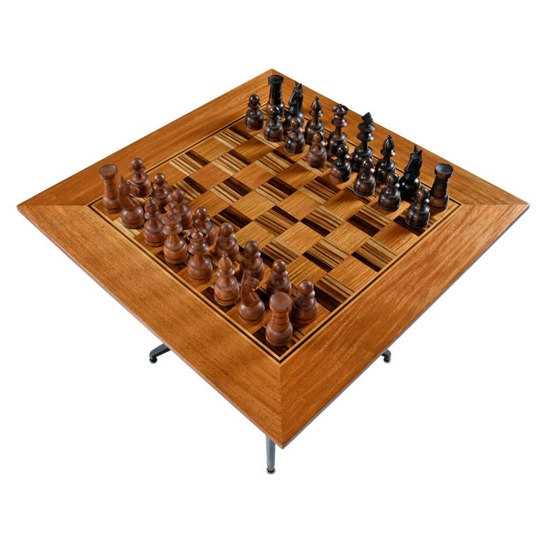 This spectacular chess table set is one of a kind. The game board is a magnificent creation of checkerboard pattern Macassar ebony and teak wood. The striped ebony is absolutely stunning and is tempered by the honey colored teak. The perimeter of