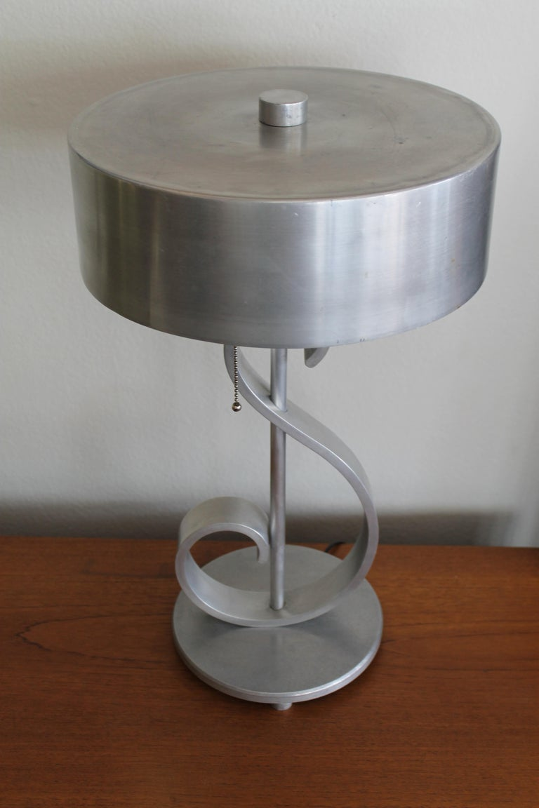 Aluminum musical note table lamp with original shade and finial. Lamp has been professionally rewired with an in-line switch and pull chains. Lamp (with shade) measures 20.5