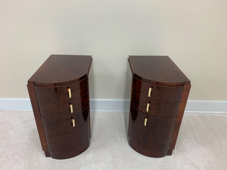 Machine Age Art Deco burl and brass night tables circa 1930s. Beautiful and functional set of left and right tables. These gorgeous burl and mahogany woods are accented by solid brass and Bakelite handles. With two drawers and a door these tables