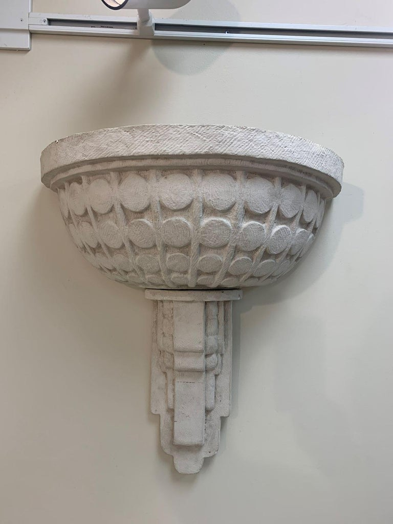 Incredible large-scale plaster Art Deco sconces. Beautiful design with geometric circles and a skyscraper base. Pieces have minor chips and wear. Each sconce is made up of two pieces and both need to be rewired. Would also look amazing as planters.